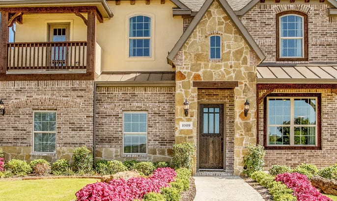 Gehan Homes Classic Sycamore Floorplan elevation with stone exterior, metal roofing & 2nd floor patio