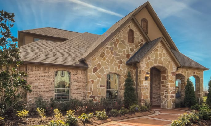 Gehan Homes Laurel elevation with tiered roof and stone cobbled exterior and a manicured garden